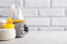 Baby Hygiene Accessories In Home Bathroom. Rubber Toy, Cosmetic Cream, Soap, Sponge, Shampoo Bottle And Towel. Copy Space, Close Up