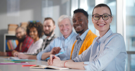 Multiethnic smiling people sitting at desk and looking at camera
