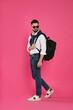 Leinwandbild Motiv Young man with stylish backpack walking on pink background