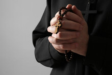 Priest With Rosary Beads Praying On Grey Background, Closeup. Space For Text