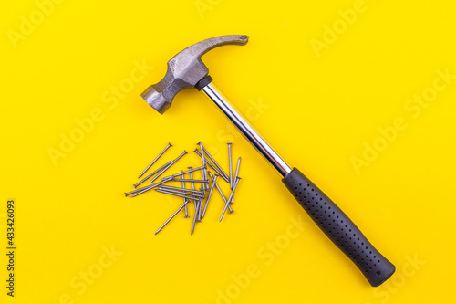 Fototapeta hammer and small nails lie on a yellow background