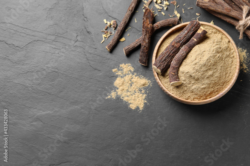 Powder in bowl and dried sticks of liquorice root on black table, flat lay. Space for text - fototapety na wymiar