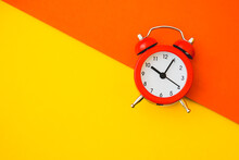 Red Analog Alarm Clock On Two Tone, Yellow And Orange, Paper Background, Top View