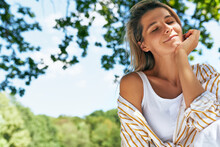 Horizontal Portrait Of A Pretty Young Blonde Woman Smiling With Eclosed Eyes, Enjoying The Sunny Day In The Park. Beautiful Female Resting In The Park During A Cozy Summer Picnic With Friends.