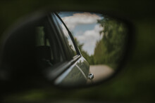 Closeup Shot Of A Car Side View Mirror Reflecting The Road