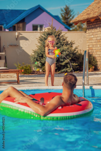 Fototapeta Father and daughter playing with squirt guns at the swimming pool obraz