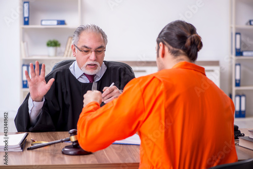 Old male judge meeting with young captive in courthouse Fototapete