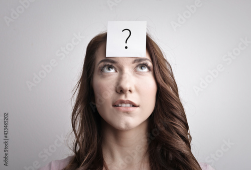 pensive young woman with a post it note pinned to her forehead with a question mark