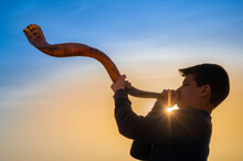Teen Boy Blowing Shofar - Ram's Horn Traditionally Used For Jewish Religious Purposes, Including The Feast Of Trumpets, Yom Kippur And Rosh Hashanah; Beautiful Sunset Sky With Sunburst In Bachground