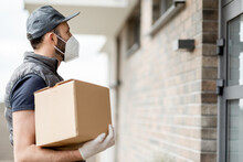 Courier In Cap Wearing Mask And Gloves Holds A Parcel Box And Staying Near Front Door Of House. Waiting For Customer To Come Out.