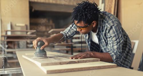 Fotografering Young black man carpenter working in his workshop.