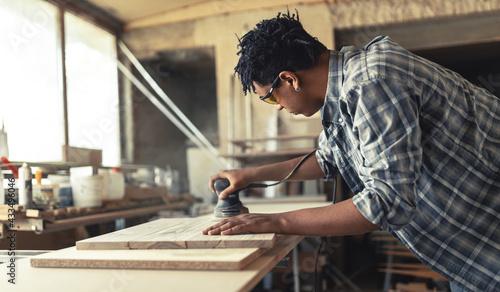 Fototapeta Young black man carpenter working in his workshop. obraz