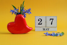Calendar For May 27 : A Bouquet In A Heart-shaped Vase With Blue Flowers And The Number 27 On Cubes, The Name Of The Month Of May In English, Yellow Background