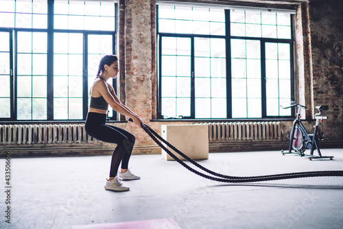 Strong woman doing exercise with ropes in gym - fototapety na wymiar