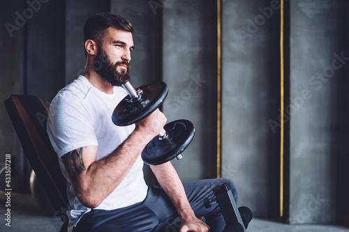 Bearded sportsman exercising with dumbbell Fototapeta