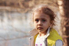 A Thoughtful 3-4 Years Child, Girl With Brooding Eyes Stands Near A Tree At The River Bank. Shallow Depth.