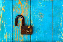 Ancient And Rusty Open Padlock On Old Wooden Table Covered With Blue Paint. View From Above