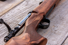 Close Up Of A Riffle Lying On Rustic Wooden Surface. Riffle, Gun