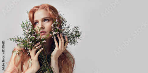 Fotografía Portrait of a beautiful young woman with red hair and flowers near the face
