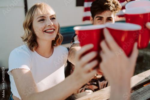 Papel de parede Amigos brindando con vasos rojos en una barbacoa por el 4 de julio día de la ind