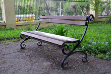 Empty Park Bench On Green Grass Background