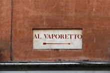 "Old Road Sign ""Al Vaporetto"" On A Wall In Venice With A Arrow To Indicate The Direction To The Boat Pier For Water Bus."