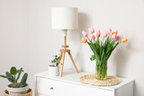 Fototapeta Tulipany - Bouquet of tulip flowers on chest of drawers near white wall