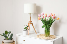 Bouquet Of Tulip Flowers On Chest Of Drawers Near White Wall