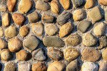 Pebble Stones Lie In Rows Partially Pressed Into The Main Surface Of The Wall, Road Or Floor