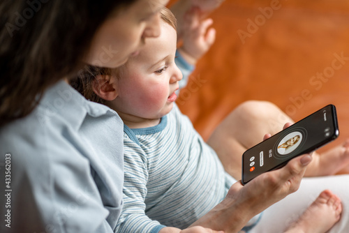 Fototapeta Young mother with newborn kid making video call to a doctor using phone at home. Concept of telemedicine and support parents counseling online.  obraz