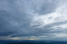 A View Of A Large Mountain Under Gloomy Clouds With Raining In Distant Sky Background Cloudy Wallpaper