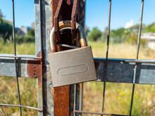 Rusty Padlock Locked On Metal Grid Fence Background.