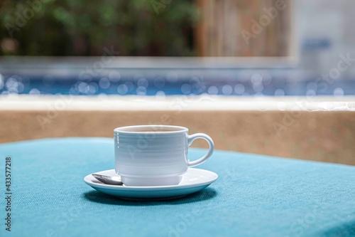 Obraz The coffee mug placed on the table has a blue tablecloth - fototapety do salonu