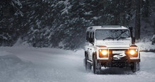 Classic Off Road With Lights On Car On The Road. Vintage Sport Utility Vehicle Driving During Snow Storm In Forest