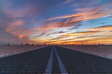 Beach Boardwalk Leading To Shore Against Sunset Sky