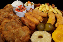 Delicious Cuban Filet. Made With Breaded Steak, Cheese, Breaded Ham And Banana, Vinaigrette, White Rice, Pineapple And Fig. Plate That Accompanies Fruits.