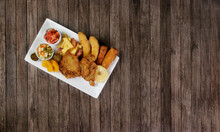 Cuban Fillet. Made With Breaded Steak, Banana, Breaded Cheese And Ham. French Fries With Bacon. Vegetables, And Fruits. Served On The Porcelain Platter. Top View Photo With Free Space For Text.