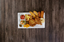 Cuban Fillet. Made With Breaded Steak, Banana, Breaded Cheese And Ham. French Fries With Bacon. Vinaigrette, Vegetables, And Fruits. Served On The Porcelain Platter. Top Shot. Vertical Background.