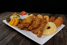Traditional Cuban Filet. Made With Breaded Steak, Banana, Breaded Cheese And Ham. French Fries With Bacon. Vegetables, And Fruits. Served On The Porcelain Platter. Popular Brazilian Cuisine.