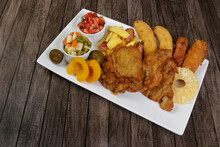 Cuban Filet. Made With Breaded Steak, Banana, Breaded Cheese And Ham. French Fries With Bacon. Vinaigrette, Vegetables, And Fruits. Served On The Porcelain Platter. Close-up Photo With Space For Text.