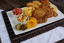 Appetizing Cuban Filet. Made With Breaded Steak, Banana, Breaded Cheese And Ham. French Fries With Bacon. Vinaigrette, Vegetables, And Fruits. Served On The Porcelain. Popular Gastronomic Photo.