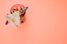 Closeup Of Glass With Iris Flower Isolated On Peach Surface For A Copy Space