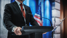 Close Up Of Organization Representative Speaking At A Press Conference In Government Building. Press Officer Delivering A Speech At A Summit. Minister At Congress. Backdrop With American Flags.