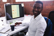 Portrait Of African American Man Smiling While Sitting On His Desk At Modern Office