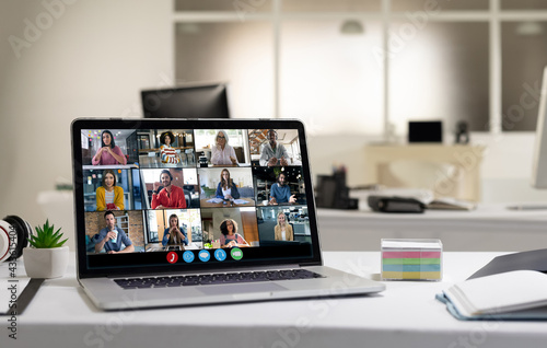 Diverse female and male coworkers having video call on screen of laptop on desk