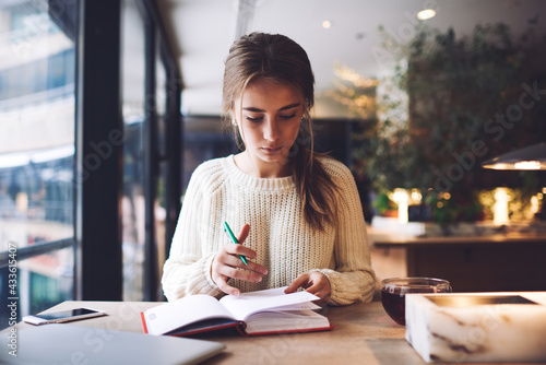 Thoughtful female student sitting at table with notebook and cup of tea Fototapet