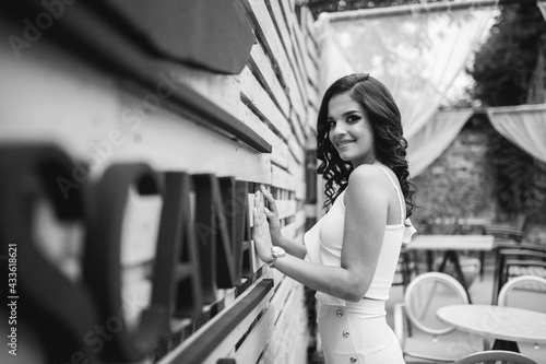 Fotografiet Young brunette curly female model posing in an event venue in an elegant white b
