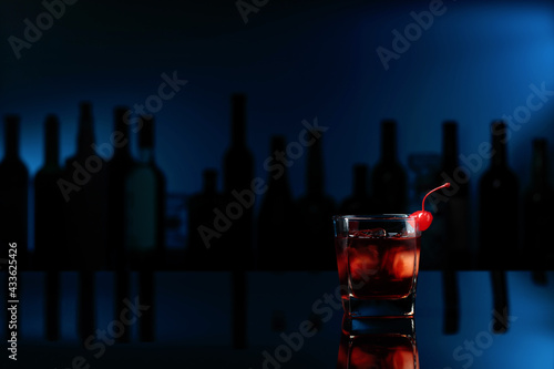 Obraz Cocktail Manhattan on a black table in a bar. - fototapety do salonu
