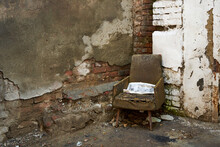 The Atmosphere Of Devastation. An Old Decrepit Chair With A Snowy Newspaper Stands On The Street Next To The Crumbling Wall Of An Old Building