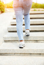 Rear View Of Young Woman Wearing Jeans And Sneakers Walking Up The Stairs Against Green Tree Background For Exercise In The Park, Outdoor. Back Of Career Girl Step Up Workout For Healthy
